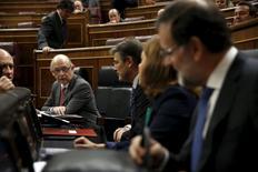 La economía española creció en el primer trimestre a su tasa más alta en más de siete años y se mantuvo en la senda para cumplir con la nueva previsión de alcanzar en el año una expansión del 2,9 por ciento, aunque otros datos mostraron que persisten algunos desequilibrios. En la imagen, el ministro de Hacienda español, Cristóbal Montoro, habla con el presidente, Mariano Rajoy, y otros altos cargos del Gobierno en el Congreso de los Diputados el 29 de abril de 2015. REUTERS/Susana Vera