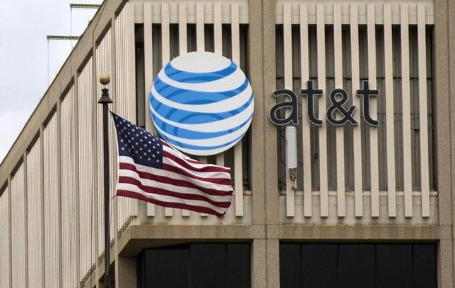 An AT&T Logo is pictured as a U.S. flag flutters in the foreground in Pasadena, California, January 26, 2015. REUTERS/Mario Anzuoni