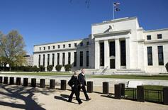 Pedestrians walk past the Federal Reserve Building in Washington April 3, 2012.  REUTERS/Joshua Roberts