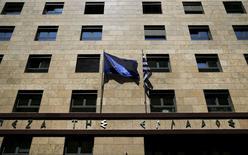 En la imagen, las banderas de Grecia y la UE flamean en la fachada del Banco de Grecia en Atenas. 14 de abril de 2015. Grecia espera que su economía crezca un poco más de un tercio del ritmo estimado inicialmente en su plan de presupuesto para el 2015, según un esquema de reformas elaborado por el Ministerio de Finanzas y publicado el sábado, lo que genera nuevas dudas sobre el rescate financiero que requiere el país.  REUTERS/Alkis Konstantinidis