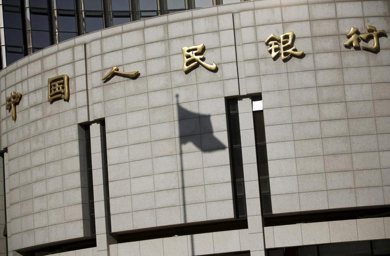 A fluttering Chinese national flag casts its shadow on the headquarters of the People's Bank of China, China's central bank, in central Beijing in this November 24, 2014 file photo.   REUTERS/Kim Kyung-Hoon/Files