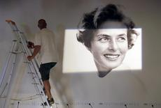 A worker sets up a giant canvas of the official poster of the 68th Cannes Film Festival, featuring late actress Ingrid Bergman, inside the press conference room at the Festival Palace in Cannes, Southern France, May 11, 2015. The poster was designed based on a photograph taken by photographer David Seymour.  REUTERS/Regis Duvignau