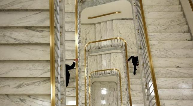 Two men hold onto the bannister as they ascend a staircase in the Rayburn House Office Building on Capitol Hill in Washington April 24, 2013. REUTERS/Kevin Lamarque