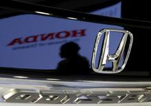 A visitor and a logo of Honda Motor are reflected on a Honda Odyssey car at the company showroom in Tokyo in this July 29, 2014 file photo. REUTERS/Toru Hanai/Files