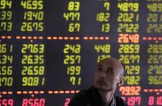 Un inversor pasa junto a un panel con información bursátil en una correduría en Shenyang, China, abr 9 2015. Las bolsas de Asia avanzaban el miércoles a pesar de otra serie de datos económicos chinos decepcionantes, ya que los inversores se centraban en la esperanza de que Pekín ofrecerá un mayor estímulo para evitar una desaceleración más aguda en la segunda mayor economía del mundo. REUTERS/Stringer