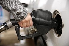 Una mujer carga combustible en una estación en Falls Church, Virginia, 16 de diciembre de 2014. Los inventarios de crudo en Estados Unidos cayeron por segunda semana consecutiva tras cuatro meses al alza, pese a que las refinerías del país redujeron sus tasas récord de procesamiento y las importaciones subieron, mostraron el miércoles datos de la gubernamental Administración de Información de Energía. REUTERS/Kevin Lamarque