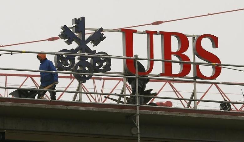 Workers are seen beside a logo of Swiss bank UBS in Zurich February 13, 2015.  REUTERS/Arnd Wiegmann