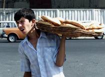 Торговец лепешками в Ташкенте. 20 сентября 2000 года. Правительство Узбекистана должно ускорить проведение реформ в частном секторе, чтобы экономический рост оставался стабильным и продолжительным, заявил Международный валютный фонд, прогнозируя сильный 2015 год. Reuters/Shamil Zhumatov