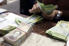 Un cajero cuenta bolívares en una casa de cambio en Caracas, 24 de febrero de 2015. El precio del dólar en el mercado paralelo de Venezuela cruzó el miércoles el umbral de los 300 bolívares, elevando las presiones inflacionarias en el país sudamericano que importa la mayoría de lo que consume. REUTERS/Carlos Garcia Rawlins