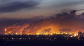 Steam rises from nearby oil refineries over the city just before dawn in Edmonton, Alberta in this file photo taken on December 8, 2009. REUTERS/Andy Clark