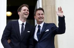 Luxembourg's Prime Minister Xavier Bettel waves as he poses with his partner, Belgian Gauthier Destenay (L), after their wedding ceremony at Luxembourg's city hall, May 15, 2015. REUTERS/Francois Lenoir