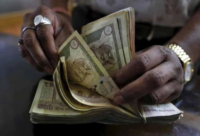 A money lender counts rupee currency notes at his shop in Ahmedabad, May 6, 2015. REUTERS/Amit Dave/Files