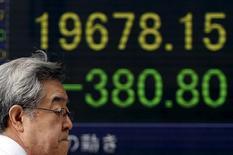 Прохожий идет мимо табло с котировками Nikkei  30 апреля 2015 года. REUTERS/Yuya Shino - RTX1AWJ6