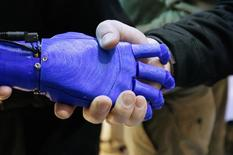 A man shakes hands with a robotic prosthetic hand in the Intel booth at the International Consumer Electronics show (CES) in Las Vegas, Nevada January 6, 2015.   REUTERS/Rick Wilking