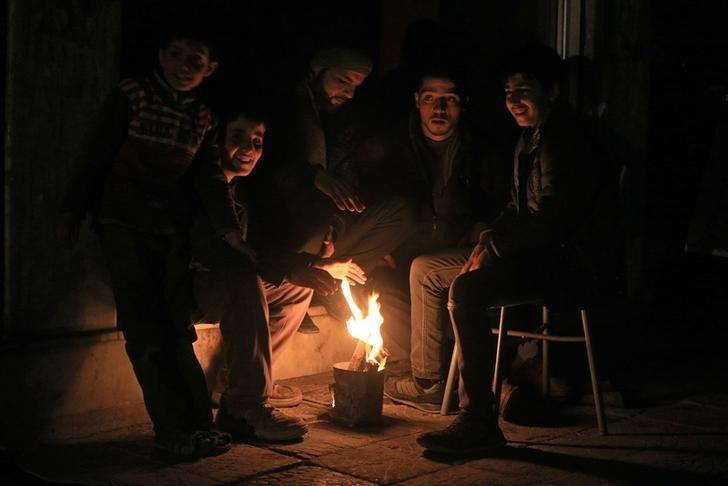 Residents warm themselves by a fire on New Year's Eve in eastern al-Ghouta, near Damascus December 31, 2014. REUTERS/Bassam Khabieh