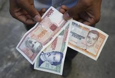 Una persona enseña unos billetes de 1000, 500 y 200 pesos cubanos en La Habana, feb 2 2015. Un acercamiento entre Estados Unidos y Cuba ha alentado a los inversores a comprar deuda de la isla en cesación de pago, pero uno de los principales acreedores se resiste todavía a recoger ganancias. REUTERS/Enrique De La Osa (CUBA  - Tags: BUSINESS POLITICS)