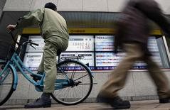 Un hombre en bicicleta mira a un tablero electrónico que muestra el índice Nikkei de la Bolsa de Tokyo, 24 de febrero de 2015. Las bolsas de Asia rebotaban desde unas pérdidas iniciales el martes, luego de que un repunte de las acciones chinas y un cierre en Wall Street en máximos históricos contrarrestaron las preocupaciones continuas sobre los problemas fiscales de Grecia. REUTERS/Yuya Shino