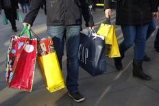 Compradores llevando bolsas en la calle Oxford, durante el último fin de semana de compras antes de la navidad, en Londres, 20 de diciembre de  2014. La tasa anual de la inflación de precios al consumidor en el Reino Unido cayó por debajo de cero por primera vez desde la década de 1960, mostraron el martes cifras oficiales, aunque los economistas dijeron que la caída a territorio de deflación probablemente dure poco tiempo. REUTERS/Luke MacGregor