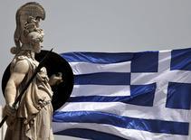 Una bandera de Grecia junto a una estatua de la diosa Atena en Atenas, mayo 21 2015. Grecia y sus acreedores no están en conversaciones para extender el rescate al país hasta el otoño boreal, sino que las negociaciones se están centrando en el cumplimiento de las condiciones del programa para el momento en que expire en junio, dijo un funcionario de alto rango de la Comisión Europea.  REUTERS/Alkis Konstantinidis