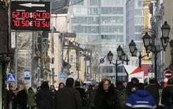 Unas personas pasando junto a una casa de cambios en Moscú, feb 24 2015. El Fondo Monetario Internacional prevé una contracción de la economía rusa del 3,4 por ciento este año, pero espera una leve recuperación en el 2016, dijo el jueves Ernesto Ramírez Rigo, titular de la misión del fondo en Rusia. REUTERS/Maxim Shemetov