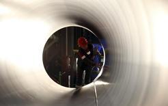 Рабочий у трубы на заводе ОМК в Выксе. 15 апреля 2014 года. Крупнейший производитель труб в РФ ТМК получил $30 миллионов чистой прибыли в первом квартале по сравнению с убытком в $16 миллионов в первом квартале прошлого года. REUTERS/Sergei Karpukhin