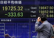 Un peatón se rasca la cabeza y mira un tablero electrónico que muestra el índice Nikkei de la Bolsa de Tokyo, en Tokyo, Japón, 30 de abril de 2015. Las bolsas de Asia subían el viernes después de que Wall Street cerró en máximos históricos ante una caída en las perspectivas de un alza de tasas de interés de la Reserva Federal en junio, y el dólar operaba a la defensiva luego de unos datos pesimistas de Estados Unidos. REUTERS/Yuya Shino