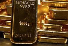 Barras de oro apiladas en un deposito de ProAurum, en Munich, 3 de marzo de 2014. Los precios del oro caían levemente el lunes, al tiempo que el dólar recuperaba fuerza frente a importantes monedas rivales, en medio de señales de que la Reserva Federal se está preparando para endurecer su política monetaria por primera vez en seis años en el 2015. REUTERS/Michael Dalder