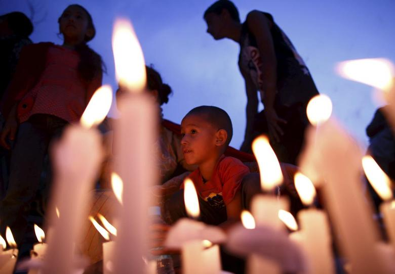 A boy sits next to the lit candles as he takes part in a candlelight vigil, a month after the April 25 earthquake, in Kathmandu, Nepal May 25, 2015. REUTERS/Navesh Chitrakar
