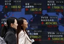 Peatones caminan junto a un tablero electrónico que muestra los índices de precios de varios países, afuera de una agencia de la bolsa, en Tokyo, 10 de abril de 2015. El índice Nikkei de la bolsa de Tokio subió el martes en una sesión volátil, anotando su octavo día consecutivo de ganancias gracias al optimismo sobre la recuperación de la economía. REUTERS/Yuya Shino