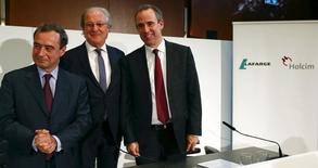 Current CEO of Lafarge Bruno Lafont (L), Wolfgang Reitzle, who will be chairman of the new merged entity LafargeHolcim, and upcoming CEO Eric Olsen (R) pose for the media after a news conference in Zurich April 9, 2015. REUTERS/Arnd Wiegmann