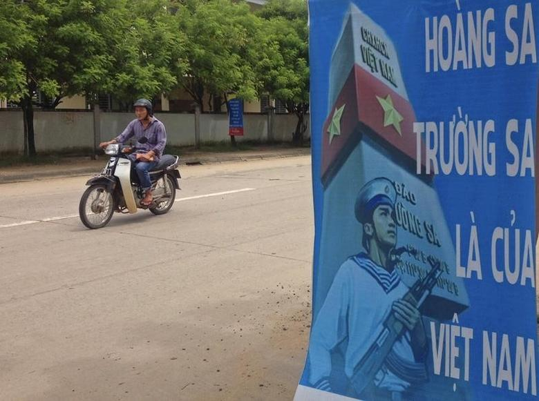 A man rides a motorcycle past a poster promoting Vietnam' sovereignty in the East Sea (South China Sea) on Phu Quoc island September 11, 2014. REUTERS/Martin Petty