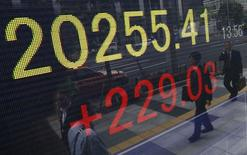 Peatones se ven reflejados en un tablero electrónico que muestra el índice Nikkei de la Bolsa de Japón, afuera de una agencia de la bolsa, en Tokyo, Japón. 20 de mayo de 2015. El índice Nikkei de la bolsa de Tokio subió el miércoles en una sesión volátil, extendiendo sus ganancias a un noveno día, pero estas fueron limitadas después de que unos datos optimistas en Estados Unidos avivaron el temor a que un alza en las tasas de interés en ese país pueda venir antes que lo esperado. REUTERS/Yuya Shino