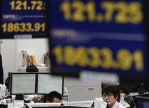 Empleados de una agencia de la bolsa extranjera, trabajan bajo monitores que muestran los índice cambiario del yen frente al dólar, y el índice Nikkei de Japón, en Tokyo, 10 de marzo de 2015. Las bolsas de Asia se hundían y el dólar se afirmaba el miércoles por la posibilidad de que la Reserva Federal de Estados Unidos se encamina a elevar las tasas de interés más tarde este año y ante la preocupación de que los problemas financieros podrían envolver a España, además de Grecia. REUTERS/Toru Hanai