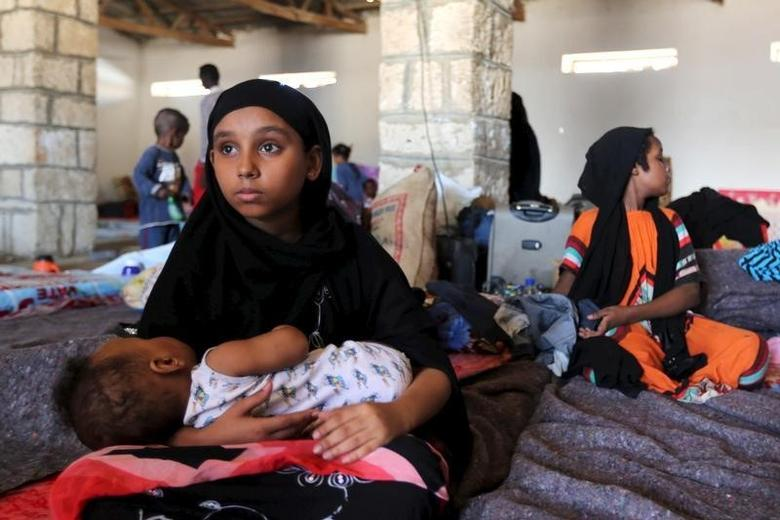 A Yemeni girl holds a baby in a temporary shelter after fleeing violence in Yemen, at the port town Bosasso in Somalia's Puntland April 17, 2015.  REUTERS/Feisal Omar