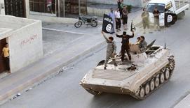 """Боевики исламского государства на бронетехнике в сирийской провинции Ракка 30 июня 2014 года. Прошедший боевую подготовку в США и России командир таджикского спецподразделения милиции сообщил, что перешел на сторону боевиков """"Исламского государства"""", угроза со стороны которого все больше тревожит правительства Центральной Азии. REUTERS/Stringer"""