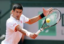 Novak Djokovic of Serbia plays a shot to Thanasi Kokkinakis of Australia during their men's singles match at the French Open tennis tournament at the Roland Garros stadium in Paris, France, May 30, 2015.      REUTERS/Pascal Rossignol