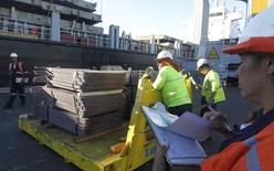 Unos trabajadores revisan un cargamento de cobre de exportación en el puerto de Valparaíso, Chile, ene 25 2015. El cobre subía el lunes debido a que el retroceso del dólar desde máximos de sesión impulsaba a un mercado ya en alza por las expectativas de una demanda más sólida en el mayor consumidor mundial China y menores suministros de concentrados del metal. REUTERS/Rodrigo Garrido