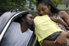 Auto worker Jermaine Austin (L), who works for General Motors, kisses his two-year-old daughter Jayla held by Armoni,15, as he bids farewell to his family as he leaves to a new job in Texas for an unknown duration, in Kansas City, Missouri May 16, 2015.  REUTERS/Ed Zurga