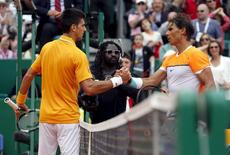 Novak Djokovic of Serbia (L) shakes hands with Rafael Nadal of Spain after their semi-final match at the Monte Carlo Masters in Monaco April 18, 2015. REUTERS/Jean-Paul Pelissier