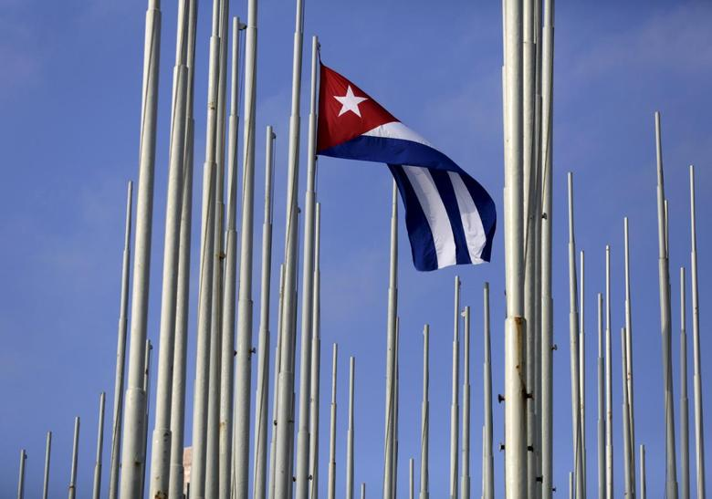 The Cuban flag flies in front of the U.S. Interests Section (background), in Havana May 22, 2015. REUTERS/Enrique de la Osa