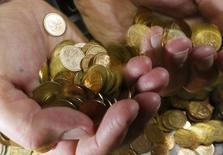 Сотрудник частной компании демонстрирует монеты номиналом 50 и 10 копеек в Красноярске 6 ноября 2014 года. Рубль поднялся с шестинедельного минимума в паре с долларом, но продолжил снижение к евро, тем самым реагируя на динамику форекса; свою роль сыграло и выравнивание текущего рыночного позиционирования, смещенного ранее в сторону покупателей валюты США, а также рост нефтяных котировок. REUTERS/Ilya Naymushin