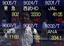 Un peatón se refleja en un tablero electrónico que muestra varios índices de precios, afuera de una agencia de la bolsa, en Tokyo, Japón. 20 de mayo de 2015. Un alza en los rendimientos de la deuda de Estados Unidos y Alemania reducía el apetito por los activos de riesgo el miércoles y mantenía a los mercados de Asia sometidos, y el euro se aferraba a las ganancias que obtuvo por unos datos optimistas de inflación en la zona euro y por la esperanza de que Grecia alcance un acuerdo con sus acreedores. REUTERS/Yuya Shino