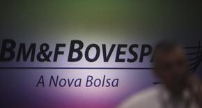 Un hombre habla por teléfono en frente del logo de la bolsa brasileña BM&FBovespa, en Sao Paulo, 7 de octubre de 2013. El principal índice de acciones de Brasil caía el miércoles tras subir casi 3 por ciento en las últimas dos sesiones, ya que los inversores optaban por posiciones más conservadoras y tomaban ganancias antes de un feriado religioso del viernes. REUTERS/Nacho Doce