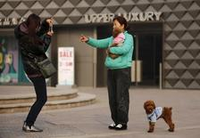 A woman takes a picture with her pet dog at a shopping mall in Beijing, in this November 25, 2014 file photo. REUTERS/Kim Kyung-Hoon/Files