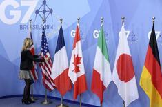Funcionária ajeita bandeiras durante cúpula do G7, em Bruxelas.   05/06/2014     REUTERS/Francois Lenoir