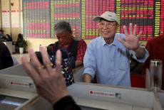 """Un hombre hace un gesto de """"cinco"""" a otro inversor cuando el Índice Compuesto de Shanghái alcanzaba los 5.000 puntos, frente a un tablero electrónico que muestra la información de las acciones en una agencia de la bolsa, en Nantong, provincia de Jiangsu, China, 5 de junio de 2015. Las bolsas de Asia caían el viernes y el euro operaba estable luego de las fuertes ganancias de la semana, mientras los inversores se preparan para unos datos de empleo en Estados Unidos y otro día de drama sobre Grecia. REUTERS/Stringer"""