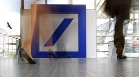 Люди проходят мимо логотипа Deutsche Bank во Франкфурте-на-Майне 21 мая 2015 года. Deutsche Bank AG ведет внутреннее расследования вероятного отмывания российскими клиентами денег на сумму около $6 миллиардов, сообщило агентство Bloomberg. REUTERS/Kai Pfaffenbach