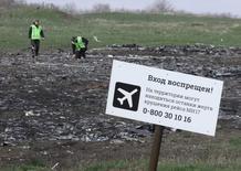 Люди изучают место падения рейса MH17 компании Malaysia Airlines близ села Грабово 16 апреля 2015 года. Глава МИД Нидерландов Берт Кёндерс обсудит в Москве в пятницу усилия, направленные на выявление подозреваемых в крушении лайнера Malaysia Airlines, упавшего 17 июля 2014 года под Донецком. REUTERS/Igor Tkachenko