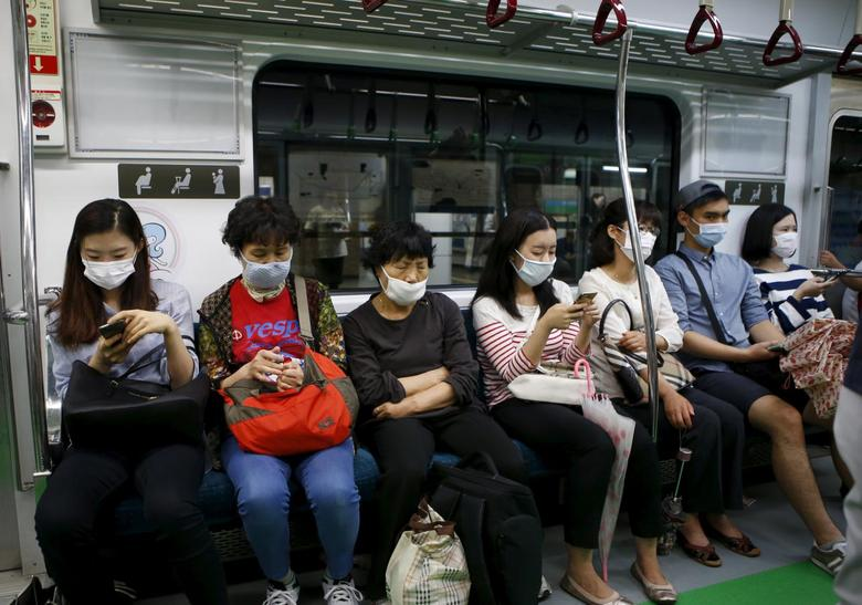 Passengers wearing masks to prevent contracting Middle East Respiratory Syndrome (MERS) sit inside a train in Seoul, South Korea, June 5, 2015. REUTERS/Kim Hong-Ji