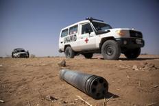 Машина UNAMID у неразорвавшегося снаряда по пути из Шангил Тобайи в Табит 27 марта 2011 года. Двое россиян, сотрудников авиакомпании Ютейр <UTAR.MM>, взятых в заложники в начале года в Дарфуре - регионе на западе Судана - были освобождены, сообщил российский МИД в субботу. REUTERS/Albert Gonzalez Farran/UNAMID/Handout